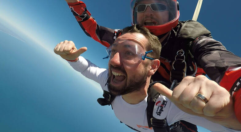 man and instructor skydiving over great ocean ride