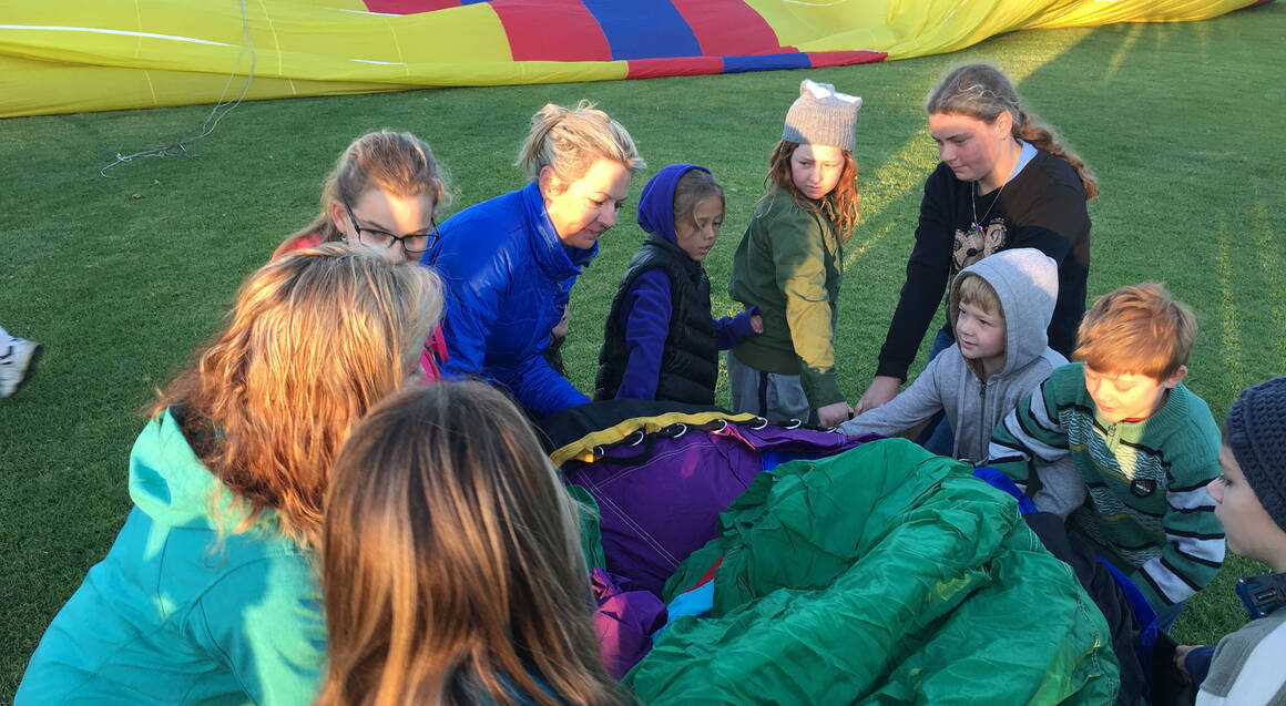 kids helping to deflate hot air balloon