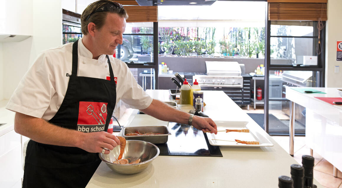 bbq cooking school man wearing apron placing prawn skewer on a dish in a modern kitchen