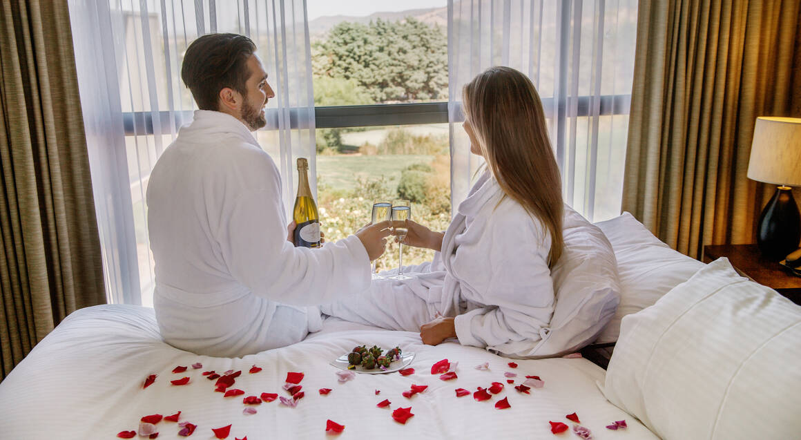 couple drinking glass of champagne on a bed overlooking yarra valley winery