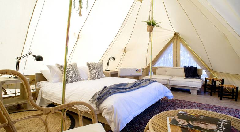 interior of a glamping tent with a bed and furniture