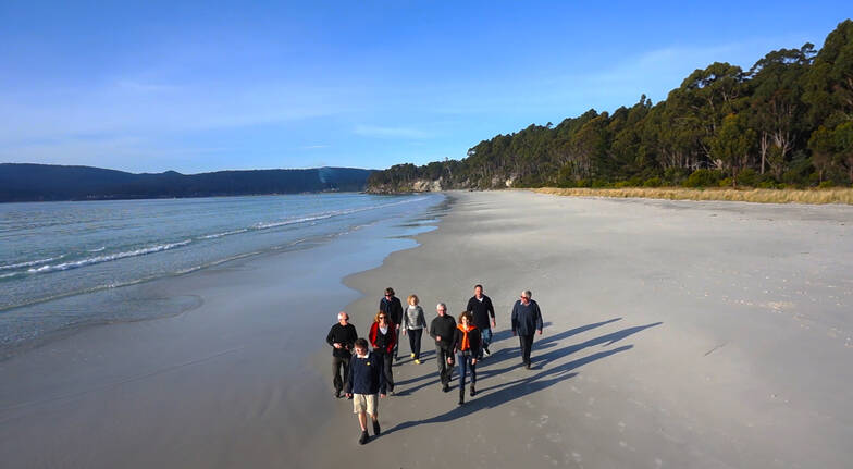 tour group walking along a beach at bruny island