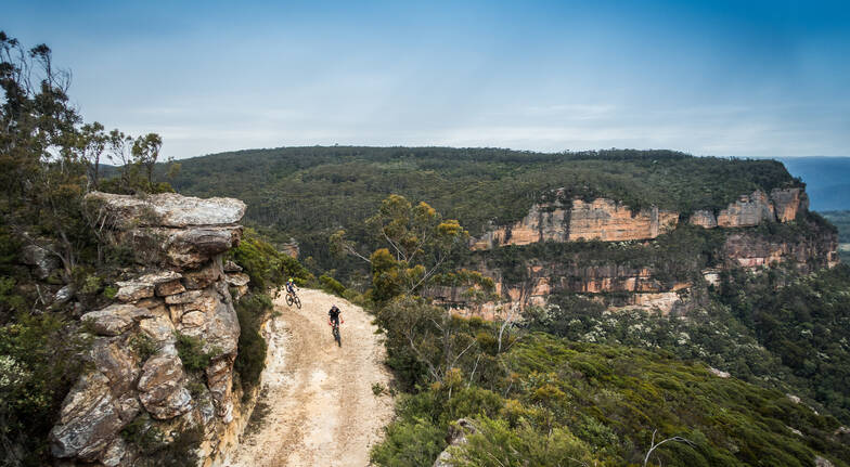 Mountain bike tour overhead shot of amazing view of bushland and a dirt track with 2 mountain bike riders