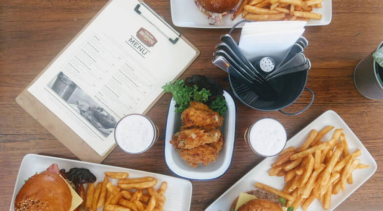 Carlton Brewhouse Victoria table with burgers fries fried chicken and beer