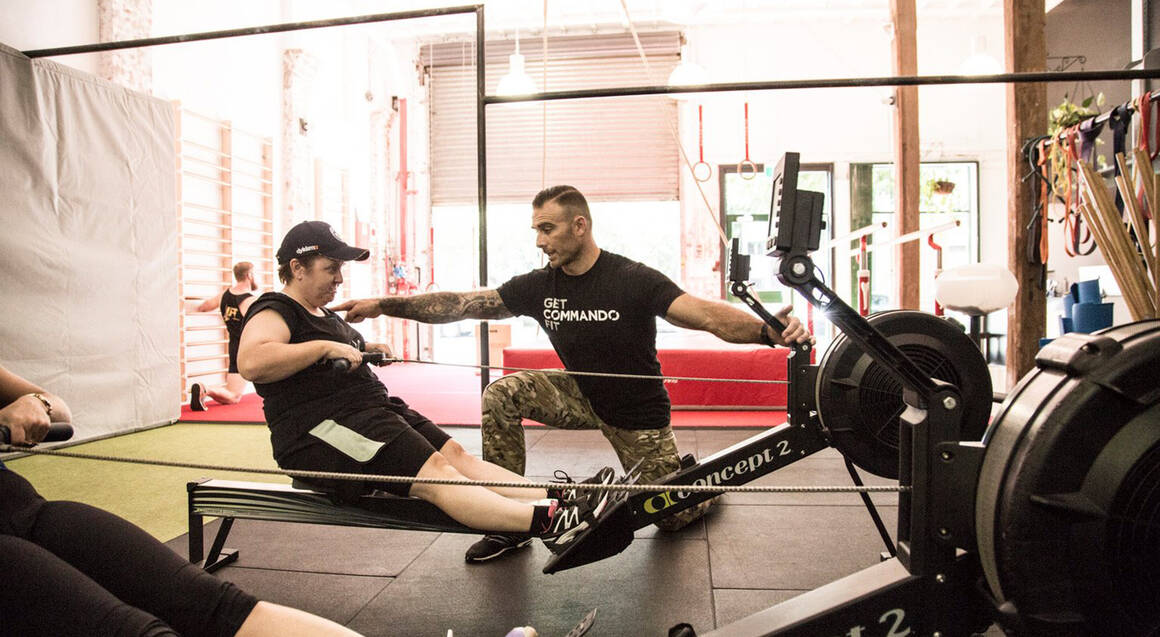 Commando steve personal trainer in gym assisting rowing