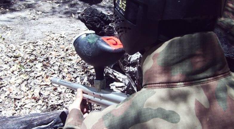 man playing paintball in bush aiming gun
