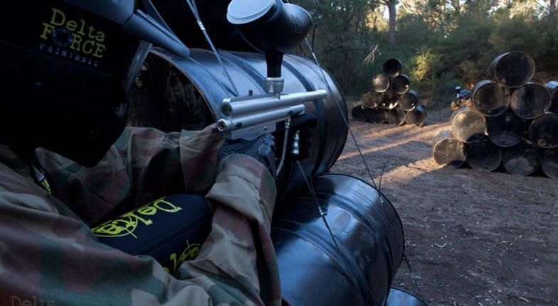 man playing paintball aiming gun