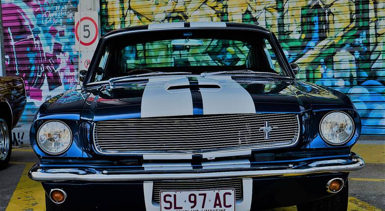 bonnet of a classic blue mustang with graffiti mural in the backdrop