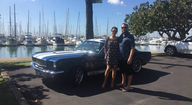 couple standing beside classic blue mustang parked beside a marina