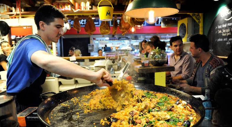Central market tours man cooking huge seafood paella