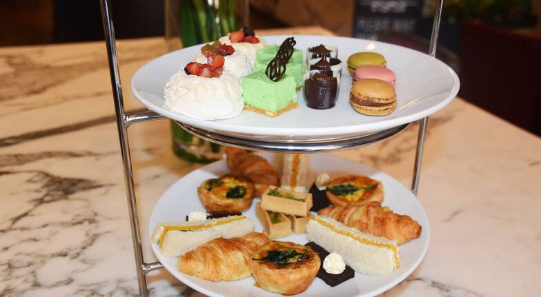 three tier high tea spread with sandwiches and sweets