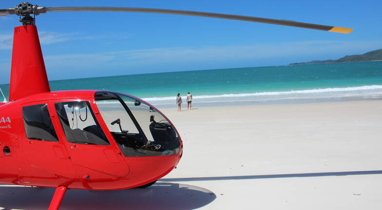 whitsundays helicopter flight a man and a woman walking on the beach with a helicopter on the beach