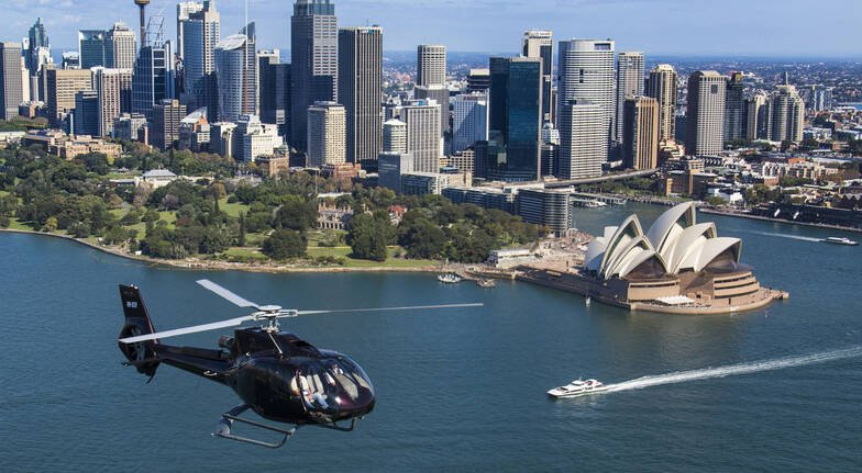 helicopter flying over sydney harbour opera house and skyline