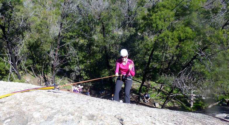 woman wabseil down a rock face in you yangs regional park