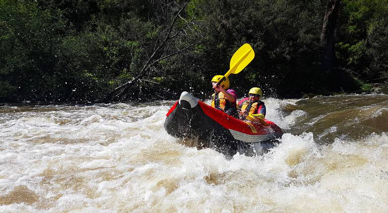 two people paddling through white water in a raft