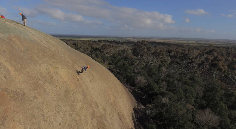 rap running women forward abseiling down an orangey cliff with bushland below and stretching towards to the sky a man is at the top of the cliff in a safety harness bending down