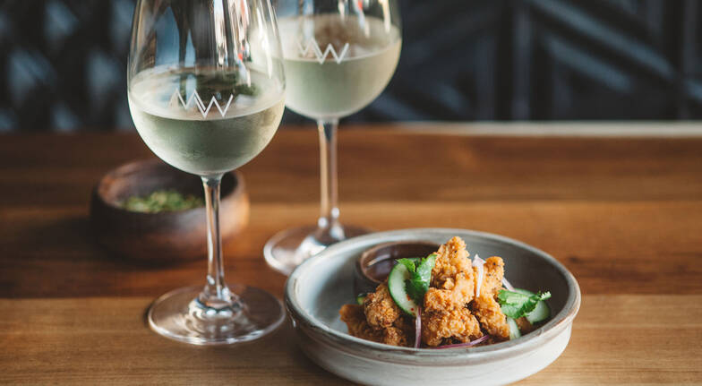bowl of fried squid with two glasses of white wine