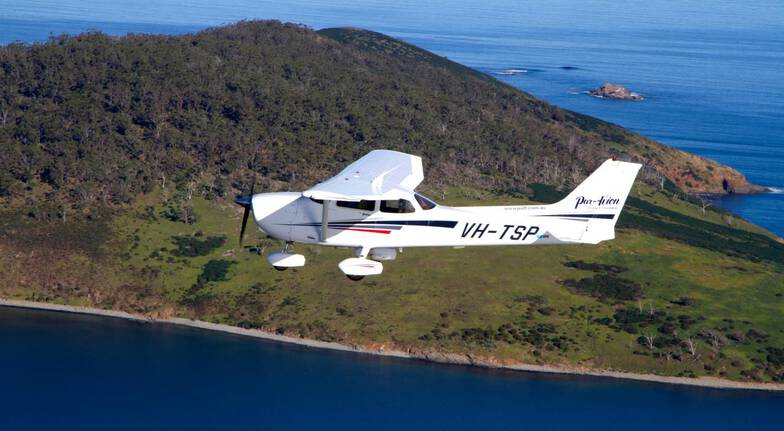 small aircraft flying over the coastline at hoabrt