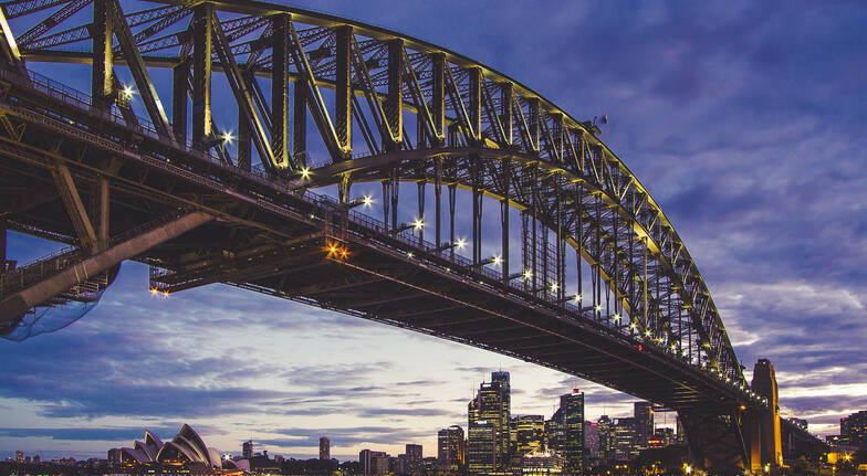 sydney private photography lesson view of a lit up sydney harbour bridge with a city skyline in the background with a dusky sky