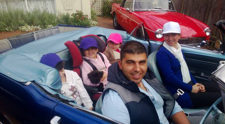 ford mustang joy ride woman man and three kids in the backset of a sports car with a red sports car in the background