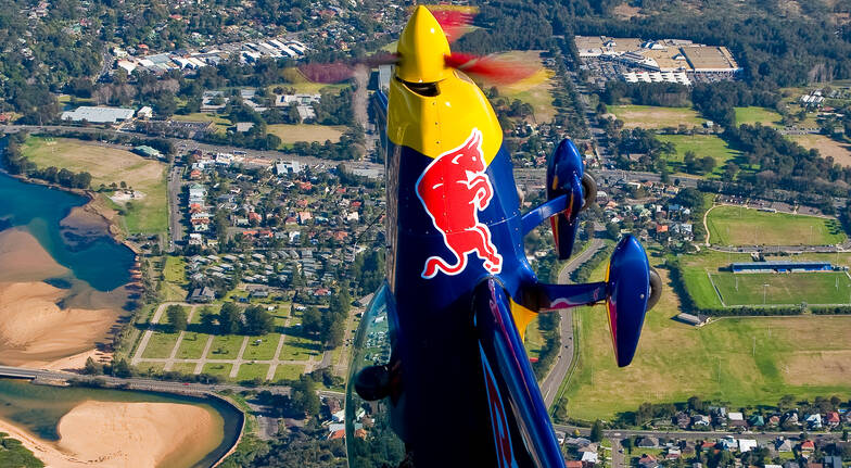 red bull aerobatic plane flying vertically above sydney