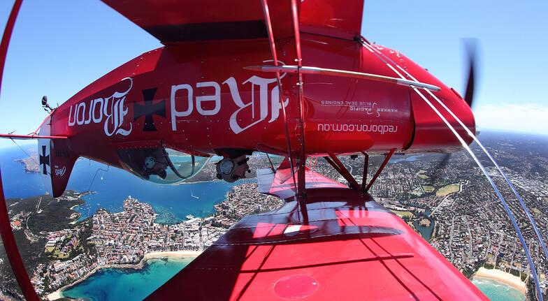 red bull aerobatic plane upside down above sydney