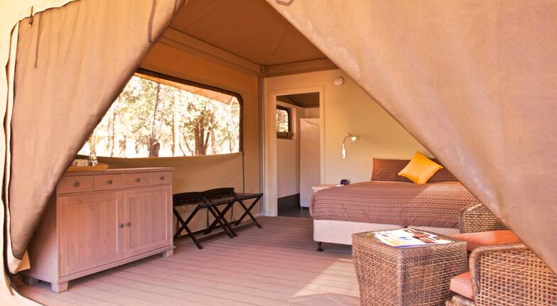 inside glamping tent with bed, window and chair