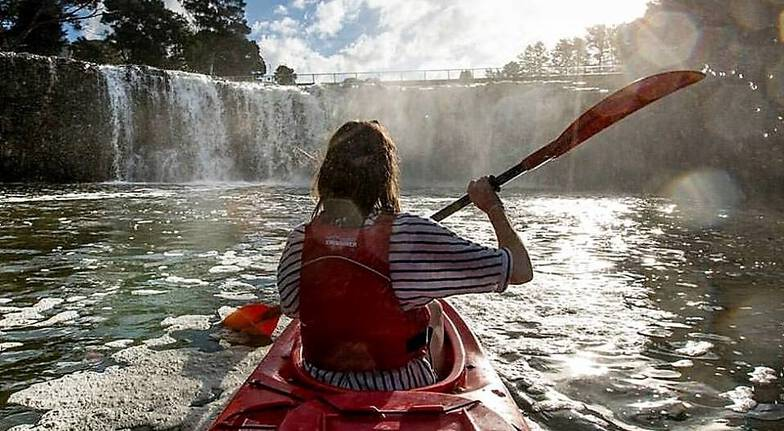 woman kayaking towards haruru falls