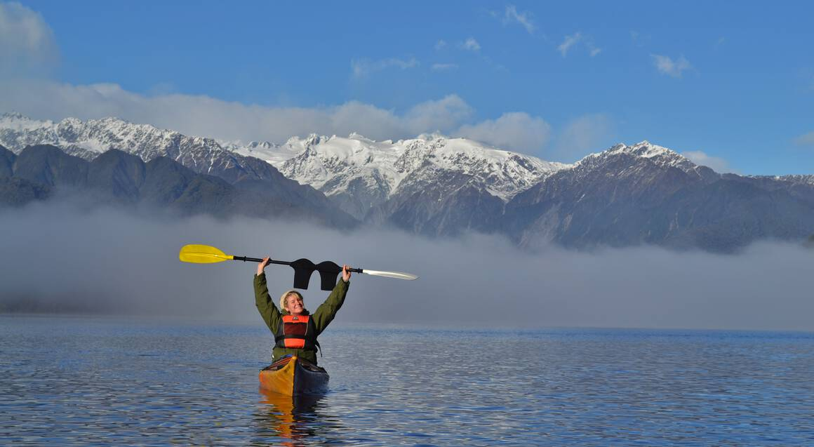 kayak on lake with mist holding paddle in the air